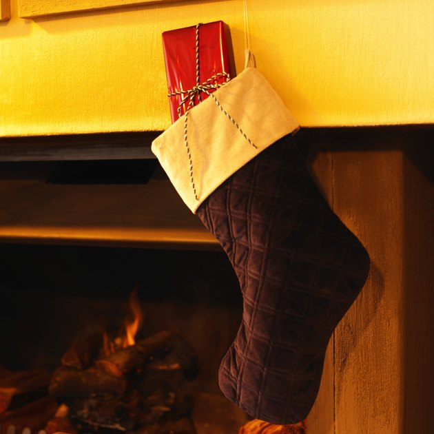 Christmas stocking hanging over a fireplace containing a gift