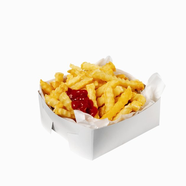 Close-up of a carton of french-fries with ketchup