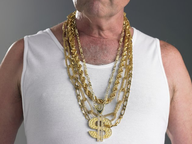 Senior man wearing tank top and gold chains with dollar sign, mid section