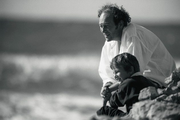 Grandfather and grandson on rocky beach