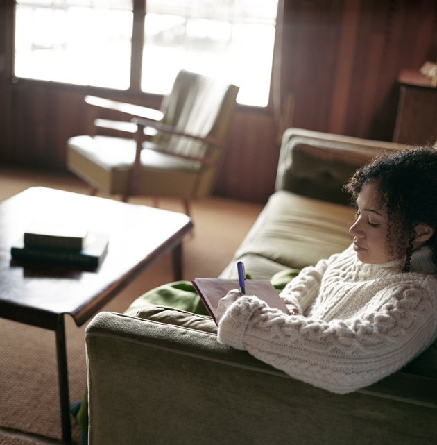 Young woman sitting on sofa, writing letter