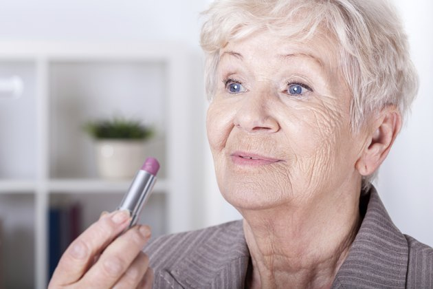 Elderly woman putting on lipstick