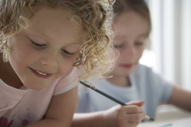 """Two girls (4-6) drawing pictures, one smiling, close-up"""