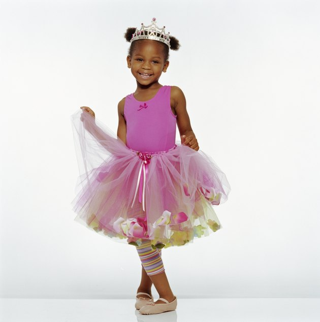 Girl (3-5) wearing tutu and crown, smiling, portrait