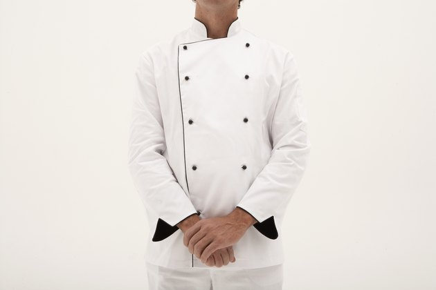Male chef standing with hands clasped, mid section