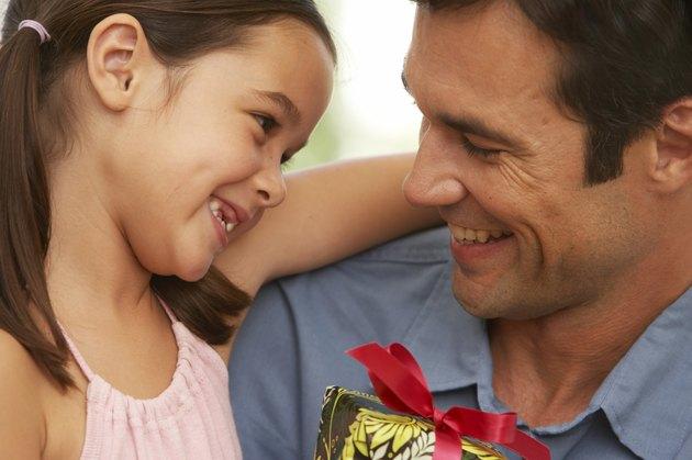 Girl (5-7) embracing father, close-up