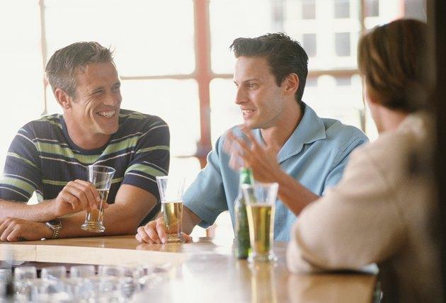 Three men sitting at bar having drinks
