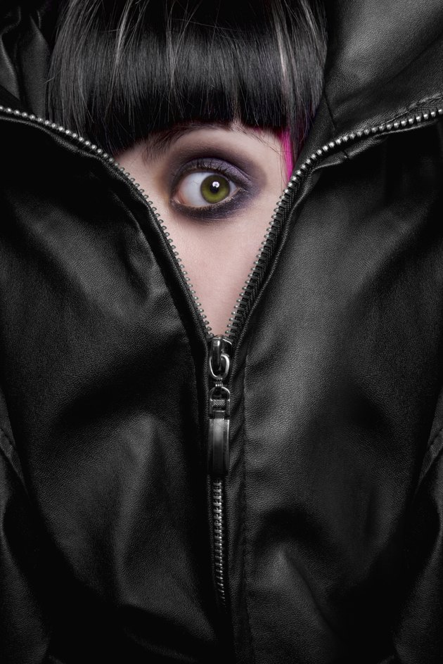 frightened green eyed girl hiding behind the zipper