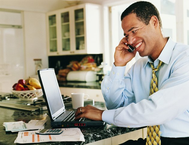 Man Sitting in a Kitchen Typing into a Laptop and Listening to his Mobile Phone
