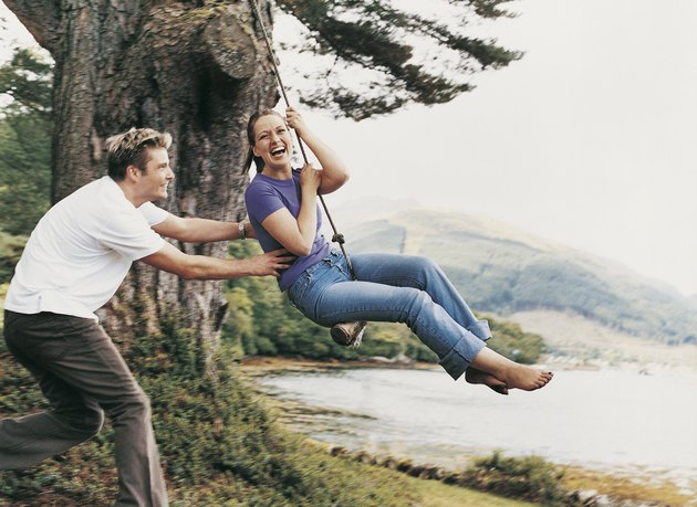 Couple Playing on a Rope Swing, Man Pulling Woman
