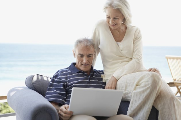 Senior Couple Sitting on an Arm Chair and Looking at a Laptop Computer