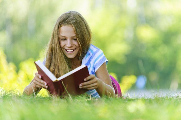 teenage girl lying on grass and read book
