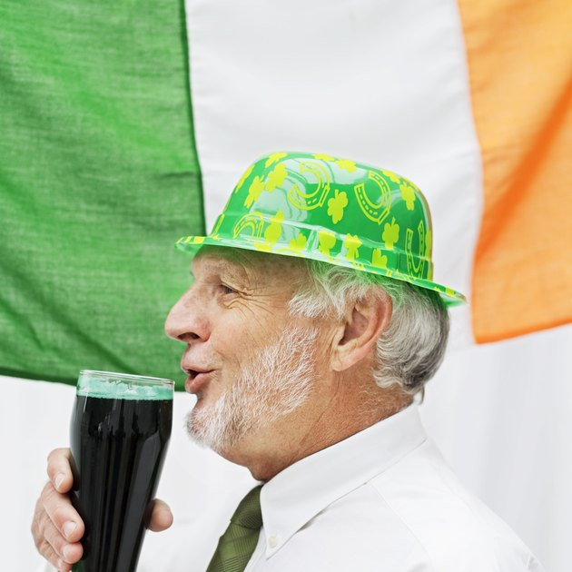 side view of an elderly man wearing a plastic hat drinking beer beside the Irish flag