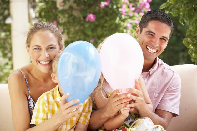 Family Sitting On Sofa Together With Balloons