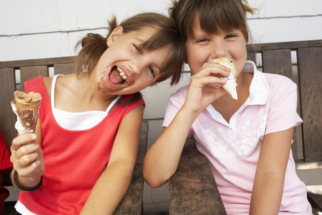 Two girls (6-9) eating ice cream, laughing, close-up, portrait