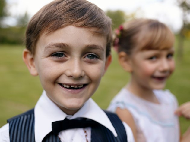 """Pageboy (6-7) with girl in background, smiling, close-up, portrait"""
