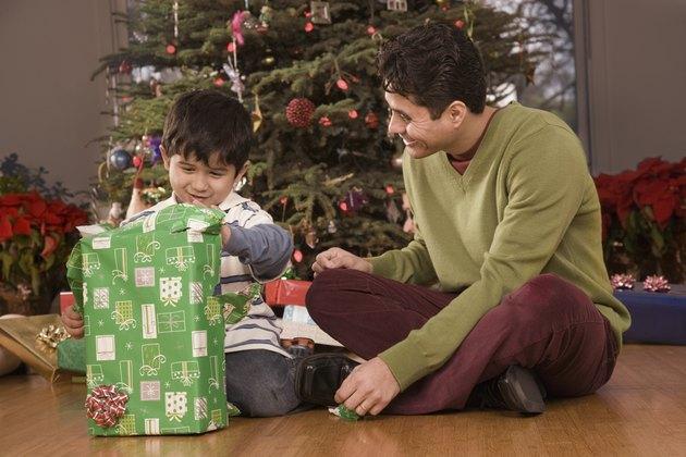 Hispanic father watching son open Christmas gift
