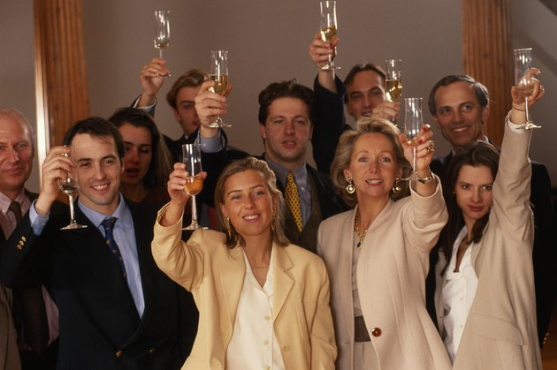 Business people raising glasses in office, smiling