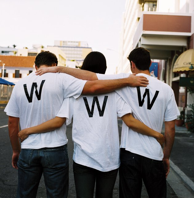 view from behind of three men wearing www on their t-shirts