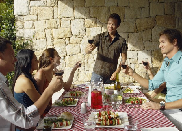 Young man raising a toast with friends drinking red wine