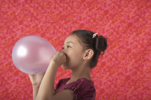 Girl (5-7) blowing balloon