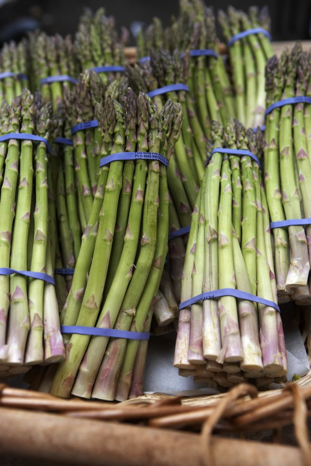 Basket of asparagus on market stall, close-up