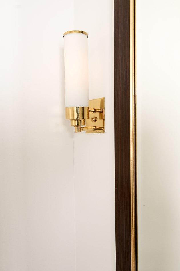 Brass light fixture on wall