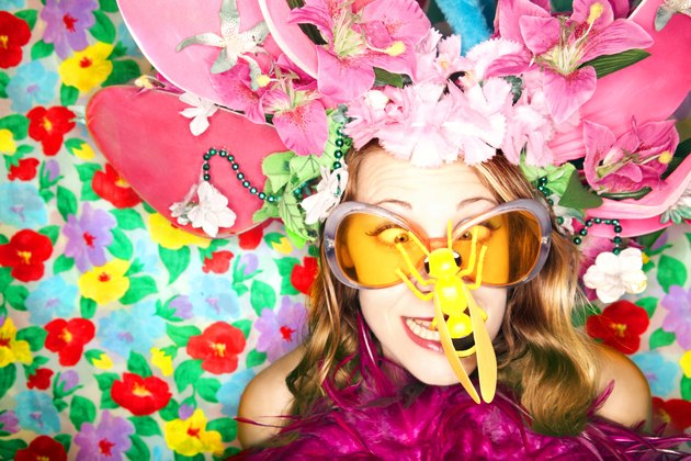 A woman looks cross-eyed at the plastic bug on her nose while wearing a wacky hat of flowers and orange sunglasses in front of a flowered background.