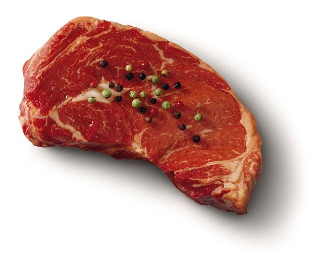 Raw steak with peppercorns