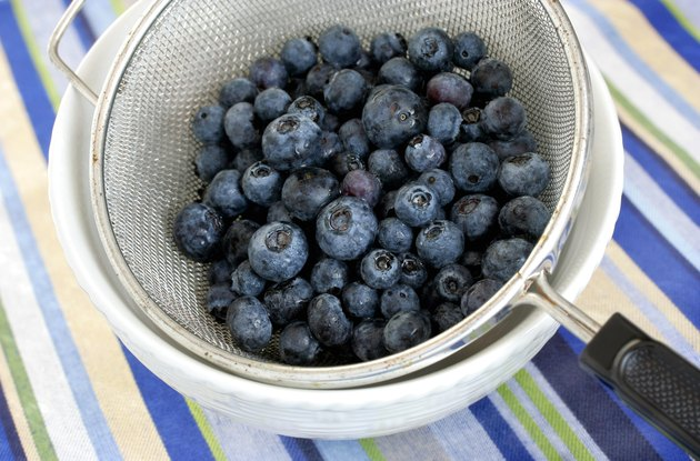 Freshly washed blueberries in vintage mesh strainer.