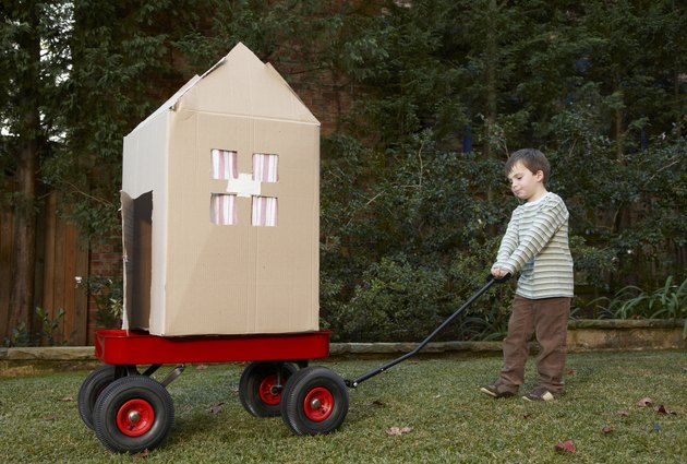 Boy (6-7) transporting cardboard house on cart