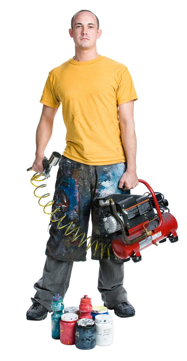 Man holding paint sprayer and air compressor