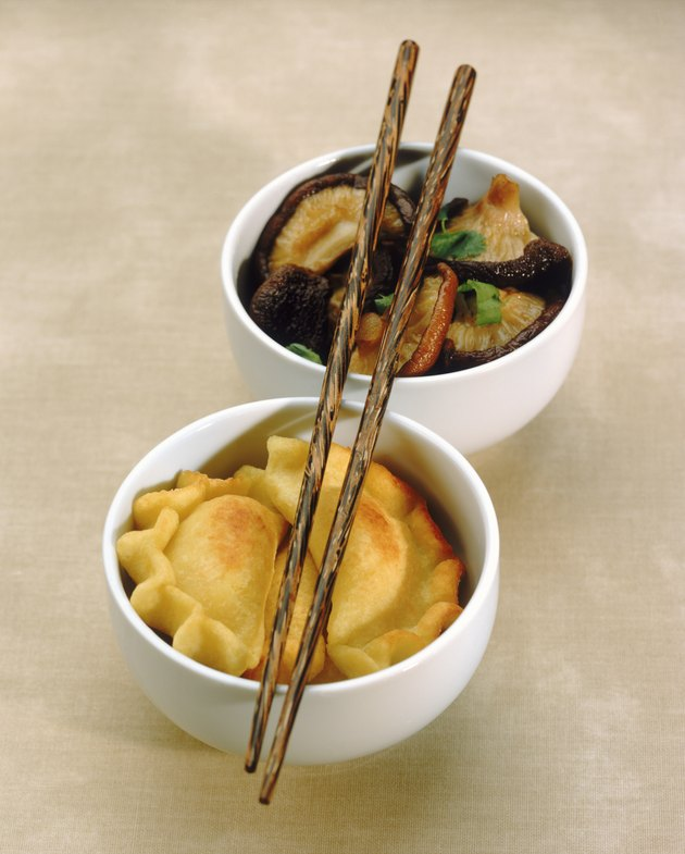 Chinese dumpling and mushroom with chopsticks in bowl, close-up