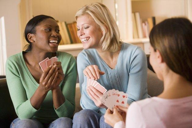 Smiling women playing cards
