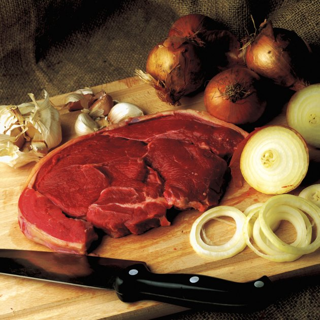 high angle view of a cut of steak on a board with onions and garlic