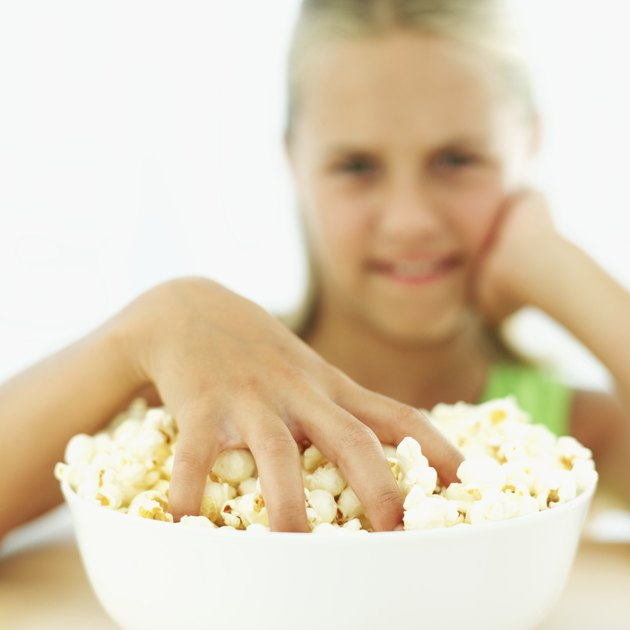 Portrait of a young girl (11-12) with her hand in a bowl of popcorn