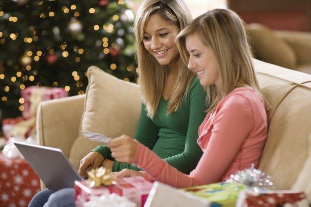 Teenage girls using laptop computer at Christmas