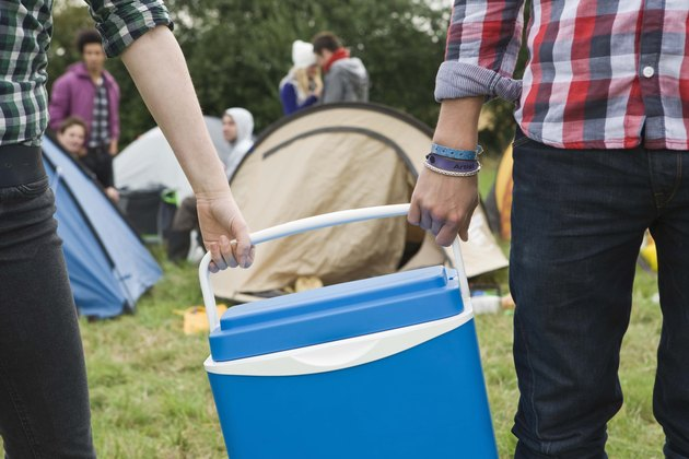 People carrying cooler by campsite