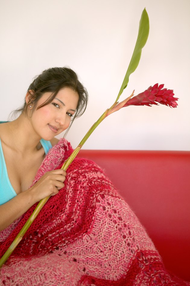 Woman Holding Flower on Couch