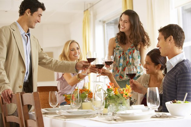 Group of young people raising glasses at dinner table, smiling