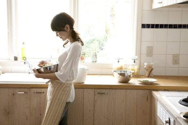 Woman holding mixing bowl in kitchen