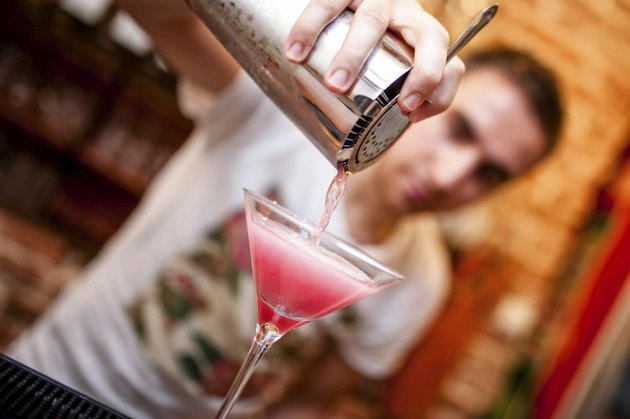 barman preparing and pouring cosmopolitan alcoholic cocktail drink