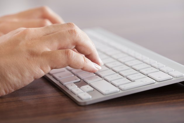 Female Hand Typing On Keyboard