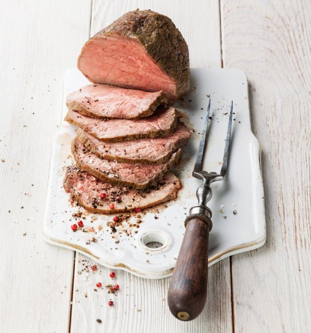 Roast beef and meat fork on white wooden background