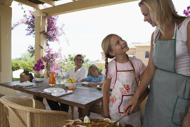 Family in villa, mother and daughter (10-12) preparing  paella