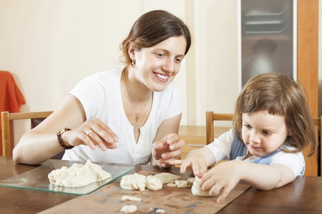 woman and her child sculpting from clay or dough
