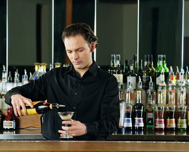 Bartender pouring cocktail behind bar