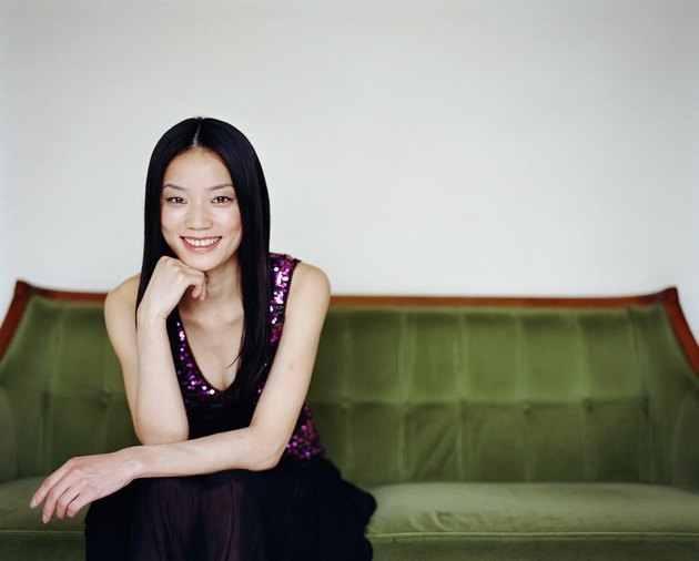 Young woman sitting on sofa, resting chin on hand, smiling