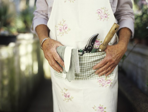 Senior woman with gardening tools in pocket of apron, mid section