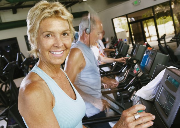 Senior woman using machine in gym, smiling, portrait, close-up